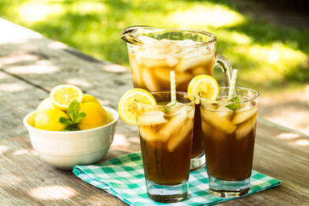 Picnic table in summertime with cold iced tea and lemons