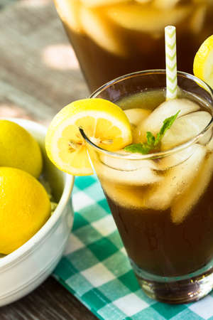 min: Ice tea in a glass with min and lemon and a straw in summertime
