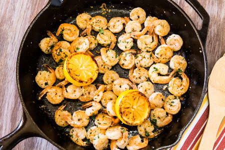 Shrimp dinner meal cooked in black cast iron skillet with grilled lemons with wood spoon and napkin Banco de Imagens