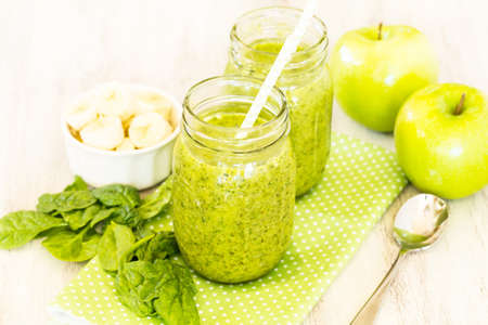 Green fruit and vegetable spinach vegan smoothies on dotted napkin with apples and banana and spoon on white background
