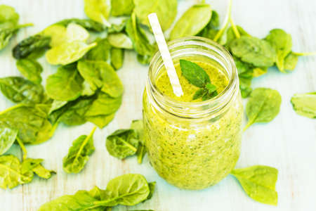 Green vegetable and fruit smoothie with spinach on blue background
