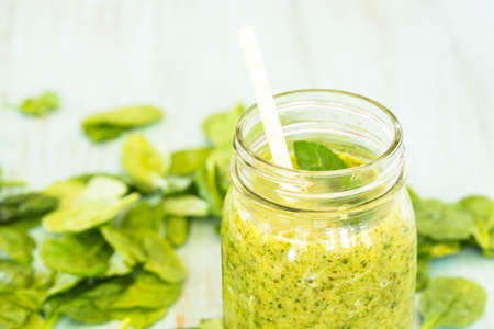 Green vegetable and fruit smoothie with spinach on blue background with straw