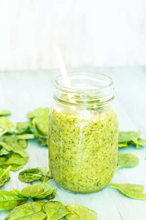 Green vegetable and fruit smoothie on blue background vertical with spinach Stock Photo