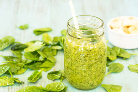 Green diet snack food smoothie with spinach and bananas on blue background