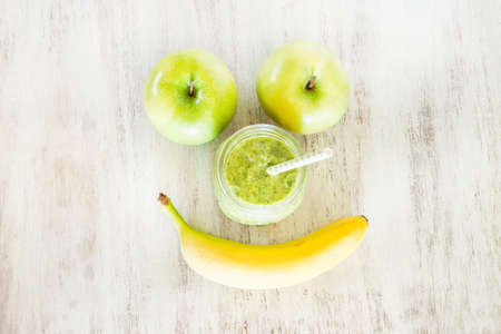 Green spinach vegetable and fruit smoothie with apples and banana in the shape of a smiley face with a straw