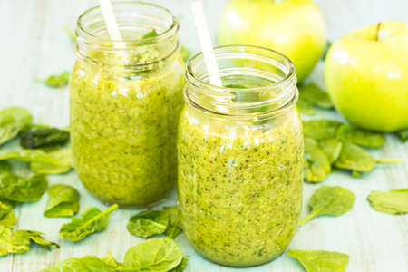 Two diet green vegetable smoothies with spinach and apples in glass jars with straws Stock Photo