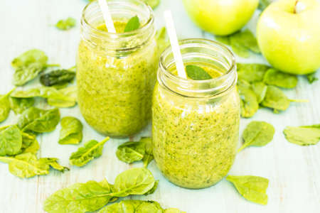Two diet green vegetable smoothies food with spinach and apples in glass jars with straws