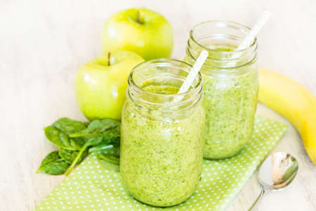 Green fruit and vegetable spinach smoothies on dotted napkin with apples and banana