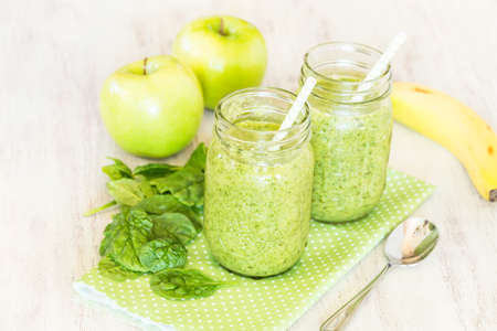 Green fruit and vegetable spinach vegan smoothies on dotted napkin with apples and banana Stock Photo