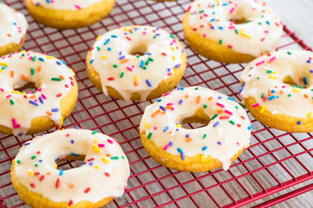 Close up cake donuts with white frosting and colorful sprinkles Stock Photo