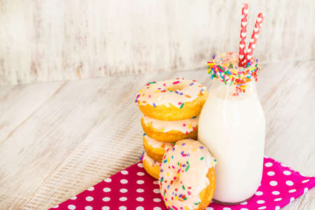 Festive breakfast treat of cake donuts with sprinkles and milk