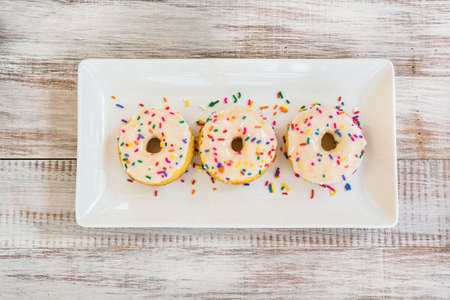 Breakfast snack of three cake doughnuts on white tray with sprinkles