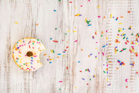 Doughnut on white wood background with colorful sprinkles and bite taken Stock Photo