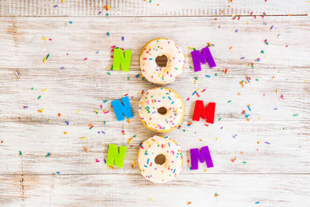 Nom Nom Nom silly donut saying on white wood background with colorful sprinkles and letters Stock Photo