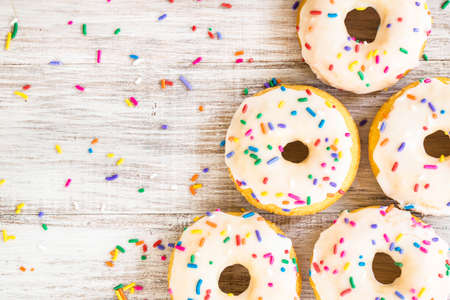 Doughnuts on white wooden background for breakfast treat with colorful sprinkles
