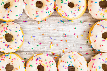 Doughnuts for breakfast arranged on white wooden background with colorful sprinkles Banco de Imagens