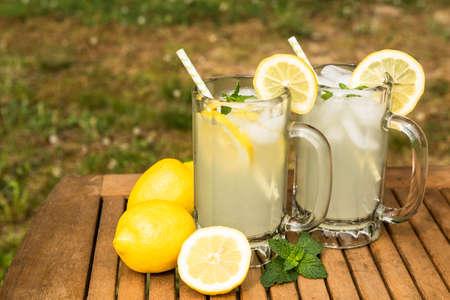 Two mugs of tasty lemonade on a hot summer day outside