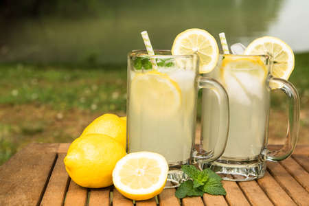 Lemonade in mugs next to a lake on a hot summer day
