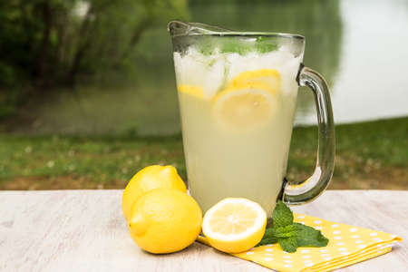 A pitcher of lemonade with lemons and mint next to a lake outside in summer