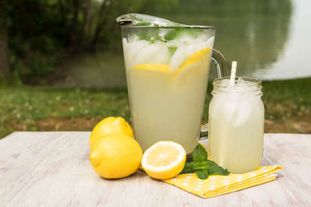 Pitcher of lemonade and glass on a yellow napkin with lemons outside by a lake in summer Stock Photo