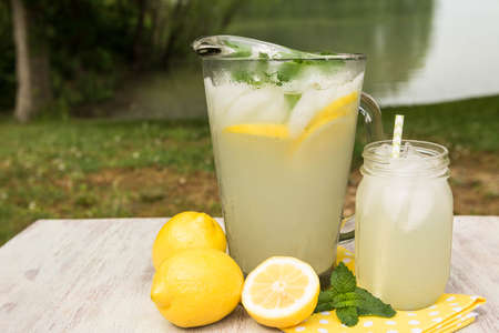 Glass and pitcher of lemonade outside by the lake in summertime Stock Photo