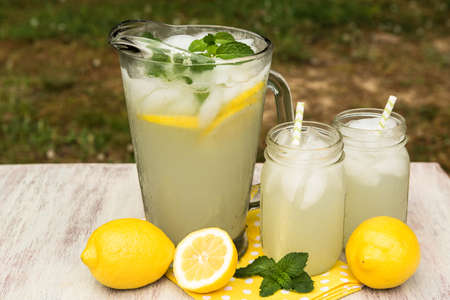 Pitcher and glasses of lemonade with lemons and mint sprigs outside in summertime
