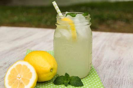 Refreshing lemonade drink with lemons outside in summertime