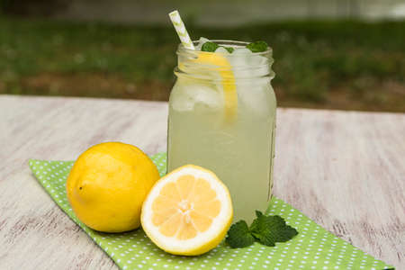 Glass of refreshing lemonade with lemons and mint sprigs on white wood board outside in summer