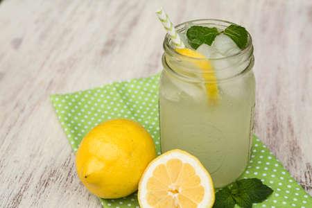 Lemonade in a glass mug with lemons on green napkin outside