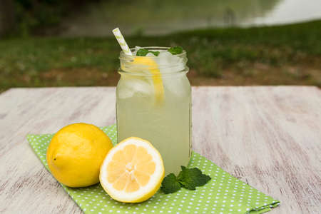 Glass of tasty lemonade with lemons and mint sprigs outside by the lake in summer Stock Photo