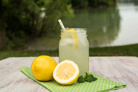 Glass jar of tasty lemonade with lemons on green napkin outside by the lake in summer Stock Photo