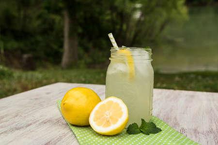 Glass mug of lemonade on white wooden table outside in summertime