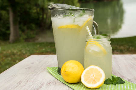 Glass pitcher and mug of lemonade with lemons on white wood table outside by the lake in summertime Stock Photo
