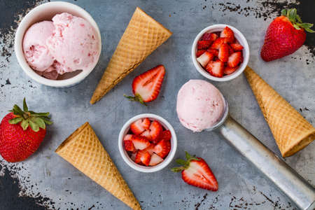 A lay flat on rustic metal with balls of strawberry ice cream and fruits and cones in summertime Stock Photo