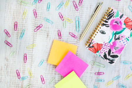 Office work desk flat lay on white background with floral notebook, pen, paper clips and sticker notes