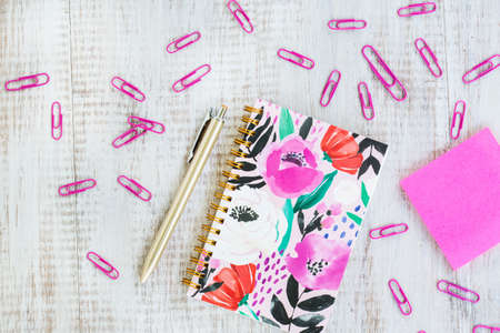 Pink womens office work from home desk with floral notebook, pen, sticker notes on white background Stock Photo