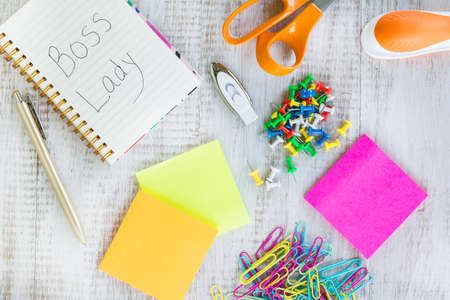 Boss lady work from home desk with office supplies including notebook, scissors, stapler, jump drive, push pins, sticker notes, pen, and paper clips Stock Photo