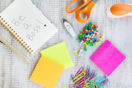 Office work supplies including notebook, jump drive, scissors, stapler, pen, sticker notes, push pins, paper clips
