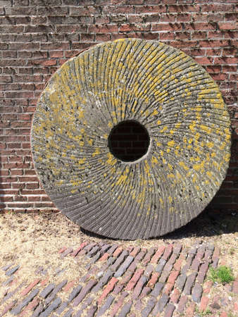 millstone: a millstone standing on house wall Stock Photo