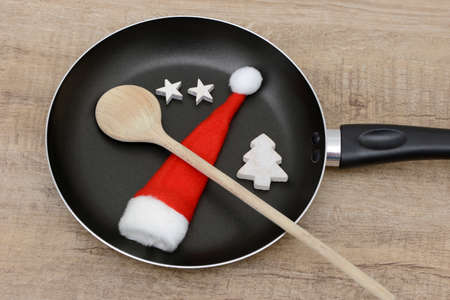 wooden hat: wooden spoon and santa hat in frying pan Stock Photo