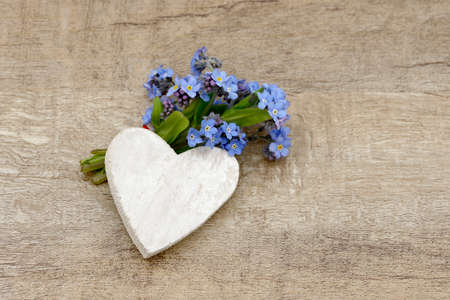 forget me not: forget me not and heart lying on wood