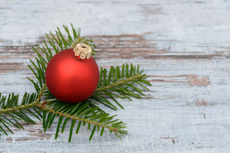 pine branch: Red xmas bauble and pine branch lying on wood