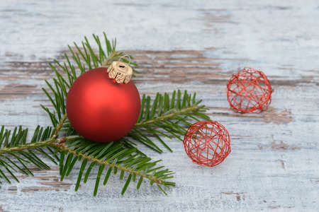branche pin: Red xmas bauble and pine branch lying on wood
