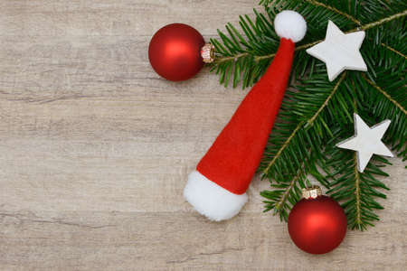 fir branch: Christmas hat lying on wood with fir branch Stock Photo