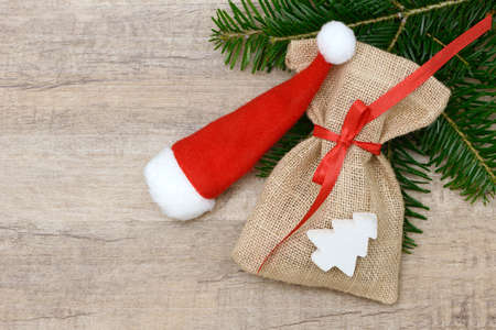 sac: santa sac and Christmas hat lying on wood with fir branch