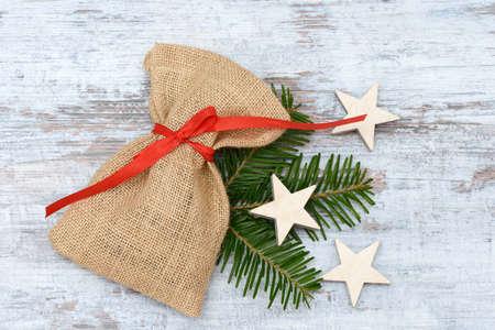 enveloped: santa bag and wooden star  lying on wood