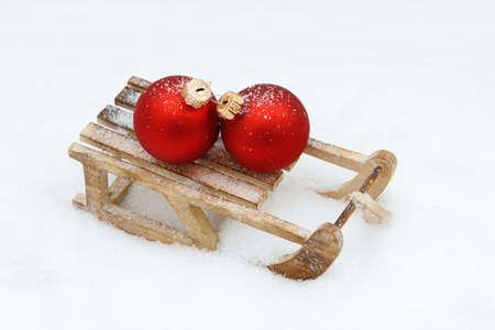 toboggan: xmas bauble on toboggan in snow Stock Photo