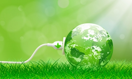 Concept d'énergie verte avec la planète Terre et prise électrique sur l'herbe luxuriante