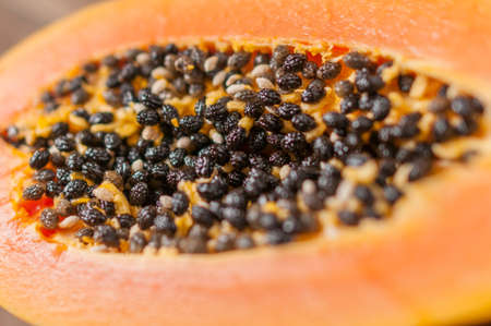 observed: Papaya fruit cut in half the seeds being observed