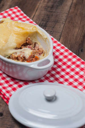 presented: English style cottage pie presented in individual white ceramic pot